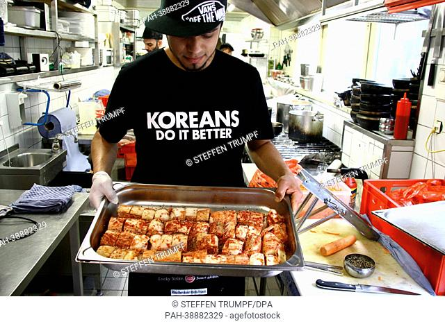 A cook displays spicy cabbage salad, the South Korean national dish Kimchi, at the restaurant 'Kimchi Princess' in Berlin-Kreuzberg, Germany, 16 April 2013