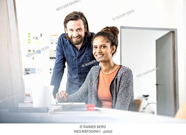 Portrait of two smiling colleagues at office desk