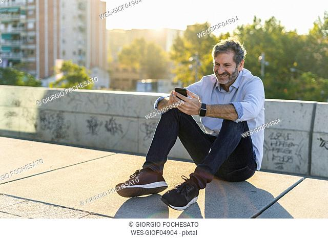 Smiling mature man sitting in the city using cell phone