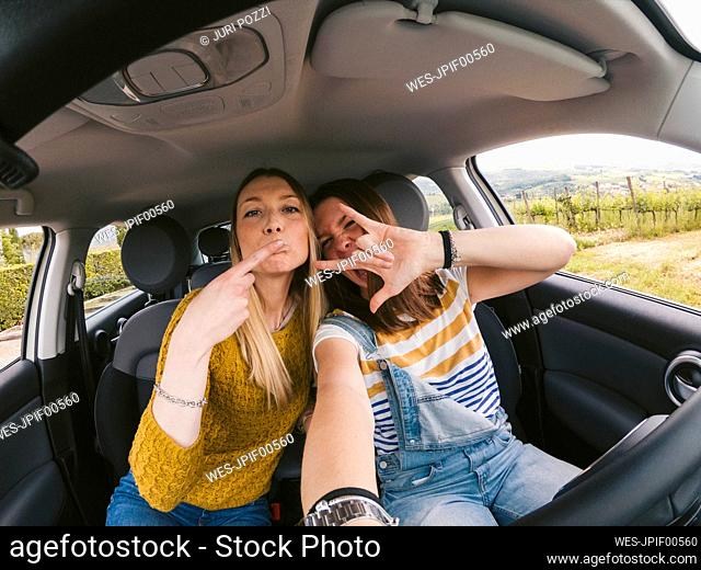 Portrait of two playful young women on a road trip