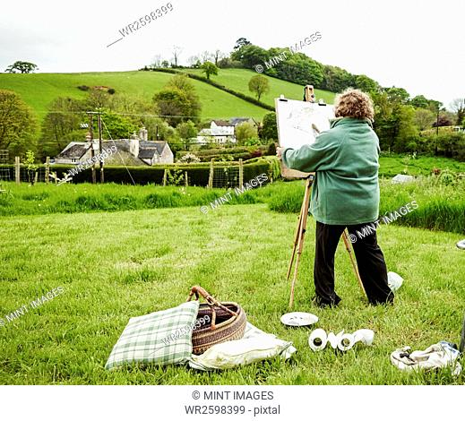 A woman artist standing outdoors at an easel, painting a rural scene
