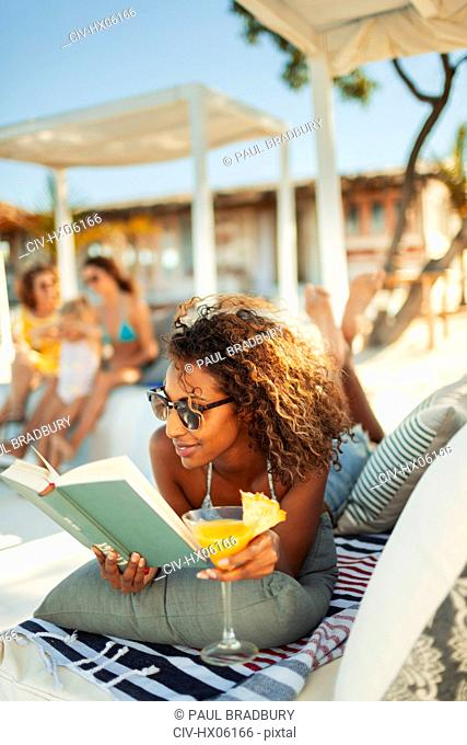 Carefree woman relaxing, reading book and drinking cocktail on beach patio