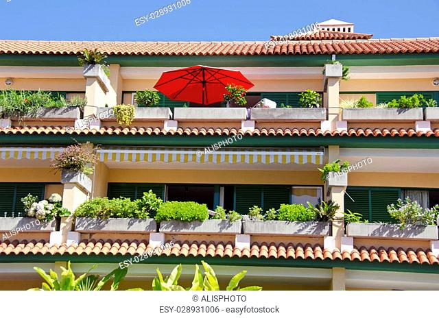 Sunlit terraced multistory orange and green house with red umbrella plants growing on sunny day, Spain