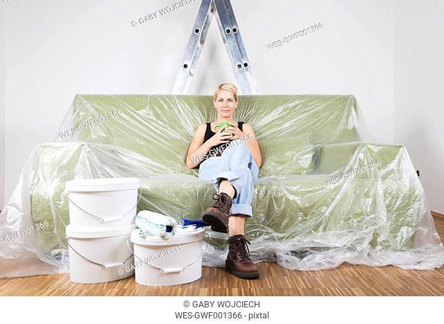 Germany, Cologne, Mature woman enjoying coffee break between wall painting work