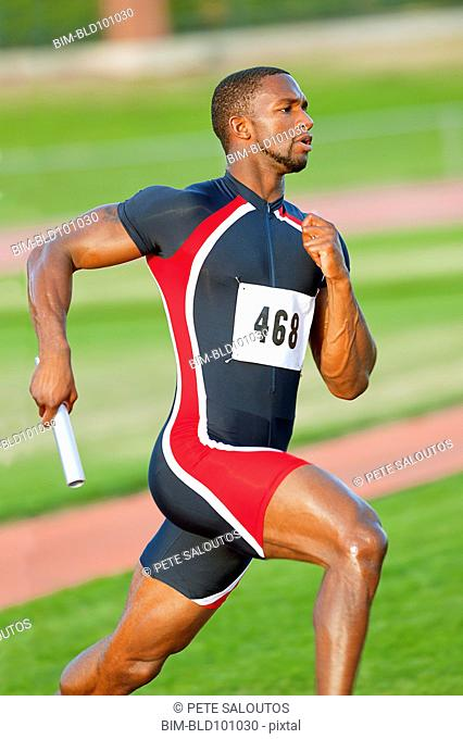 Black runner carrying baton in relay race