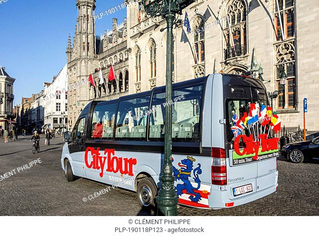 City Tour's minibus for guided sightseeing trip in front of the Provinciaal Hof / Province Court on the market place in Bruges, West Flanders, Belgium