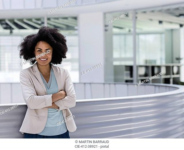 Portrait smiling confident businesswoman with arms crossed in office atrium