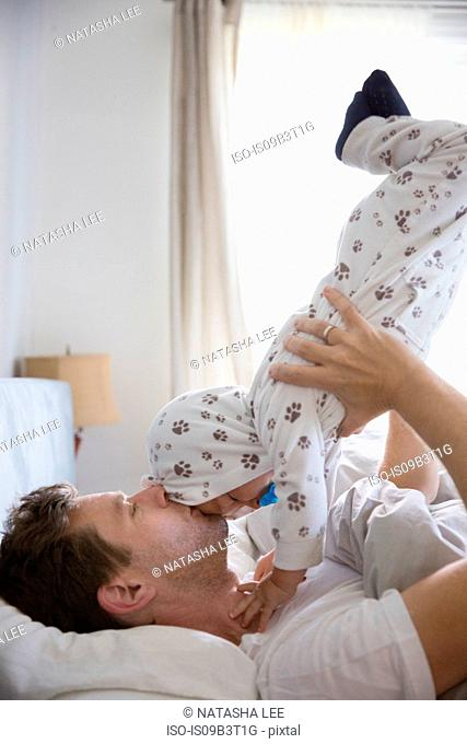 Father lying on bed, lifting young son in air