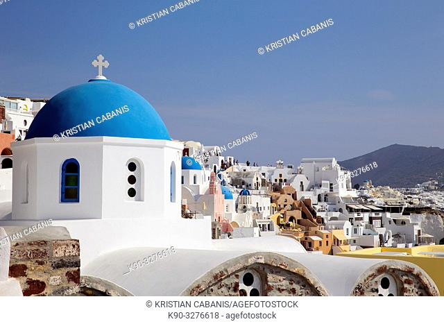 Church with blue roof top and houses in Oia, Santorin, Greece, Europe