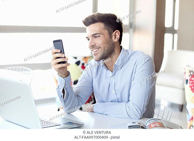 Man with expression of happiness looking at smartphone