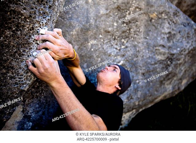 A male climber works a boulder problem called Toilet Brush V1 in Quantum Field, at Castle Hill, Canterbury, New Zealand