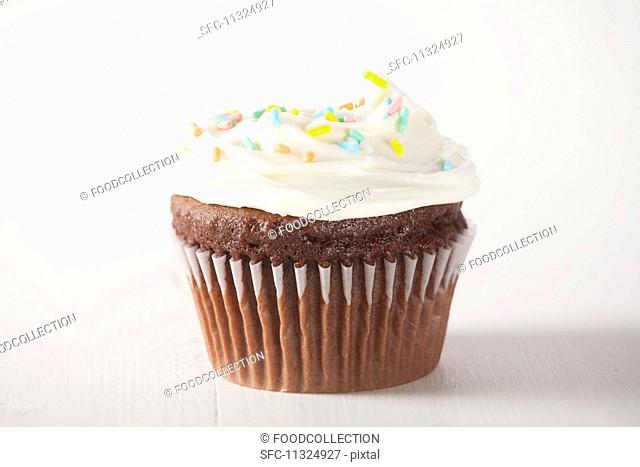 A chocolate cupcake with white frosting and sugar sprinkles