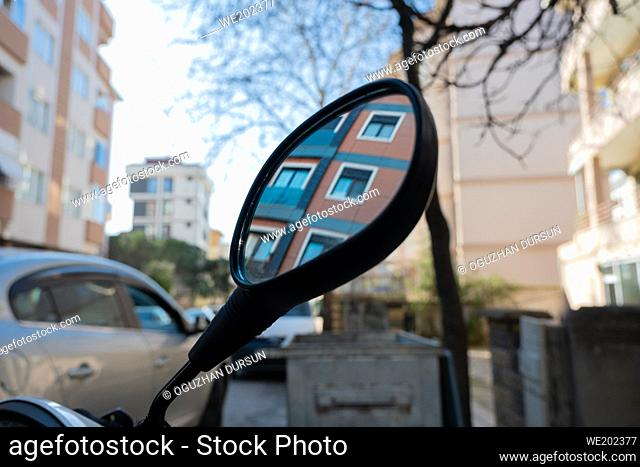mirror of motorcycle depicting the brown building in the city