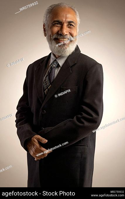 A HAPPY OLD MAN WEARING FORMALS LOOKING AWAY AND SMILING
