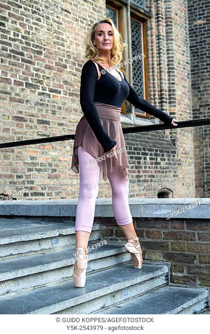 The Hague, Netherlands. 54 year old female ballet dancer at the stairs of an ancient building and monument, down town The Hague