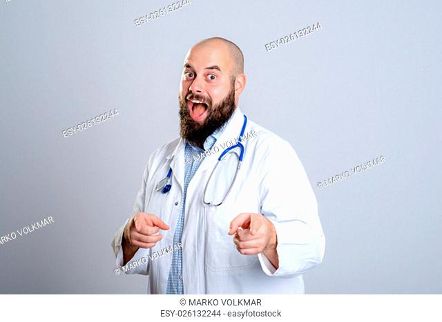 young bearded doctor in white coat smiling and pointing in to the camera