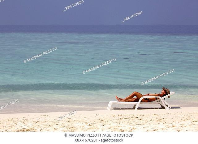 Girl lying on the beach at the seashore, Biyadhoo island, Maldives