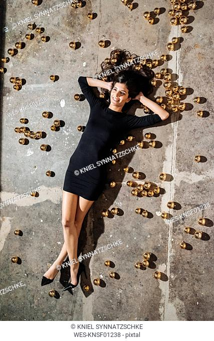 Smiling young woman lying on floor surrounded by Christmas baubles
