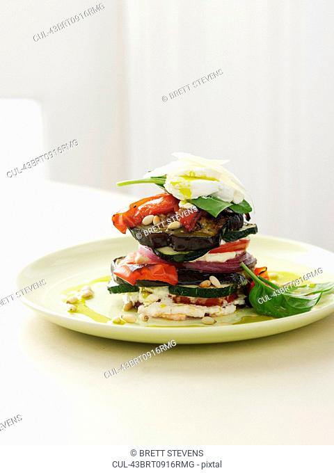 Stacked cheese, vegetables and herbs