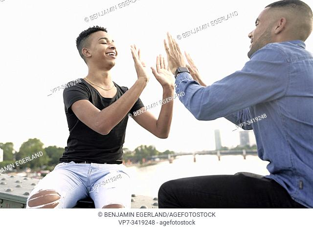 Gay couple sitting on bridge structure, playing patty cake game. Frankfurt, Germany