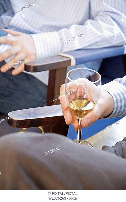 Friends at a winetasting, holding white wine