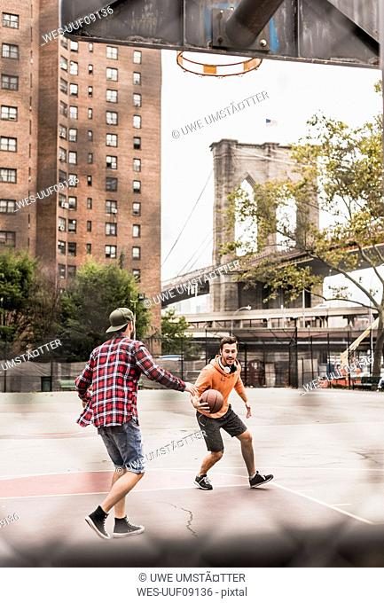 USA, New York, two young men playing basketball on an outdoor court