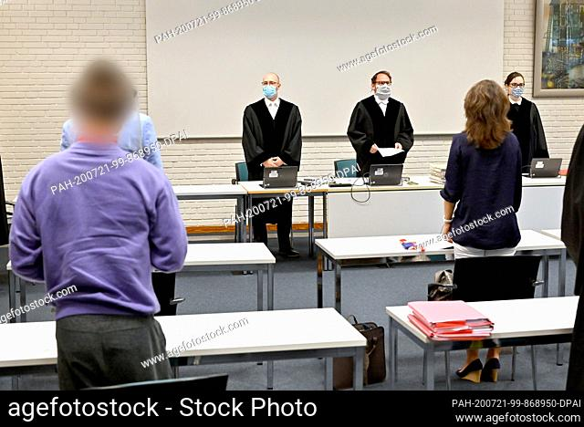 21 July 2020, Schleswig-Holstein, Oeversee: A 29-year-old defendant (l) is standing in the courtroom together with other trial participants at the start of the...