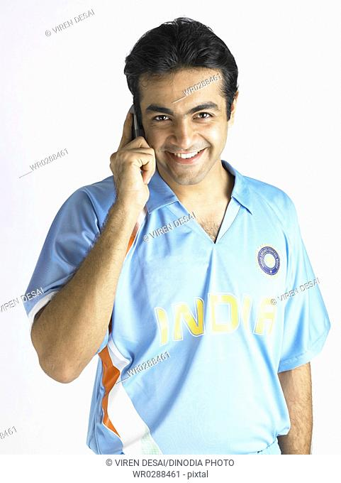 Indian cricket player talking on mobile phone MR702A