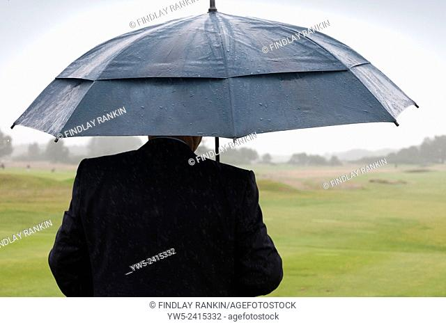 Golfer sheltering under an umbrella, looking out onto a golf course while it's raining