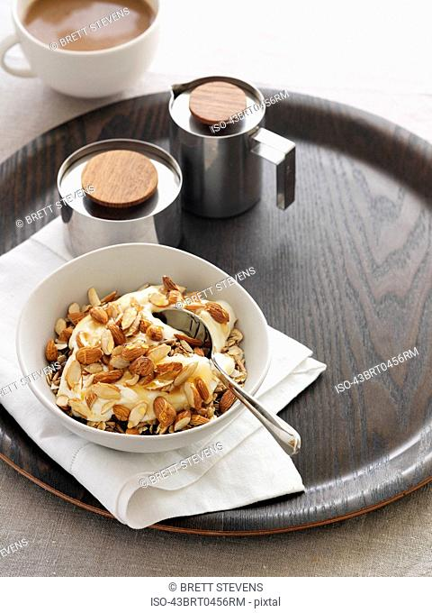 Bowl of yogurt and nuts on board