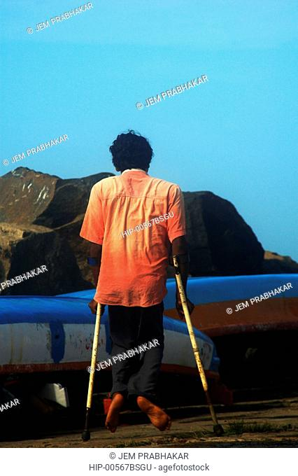 A DISABLED PERSON NEAR THE BOATS IN VIZHINJAM, TRIVANDRUM, KERALA, INDIA