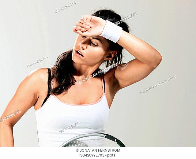 Tennis player mopping brow against white background