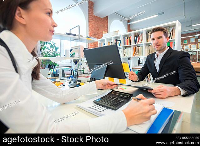 Business people working together in office sitting at the table