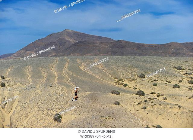 An Ultra Distance runner crossing vocanic desert with water bottle and sun hat