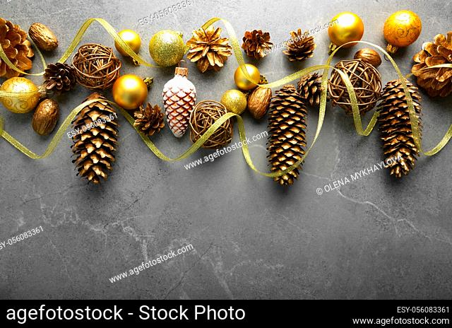 Flat lay view at Christmas decorations of gold and yellow cones glass balls and ribbon on stone table. Space for text