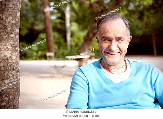 Portrait of smiling mature man sitting in the garden