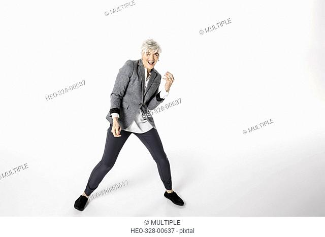 Portrait playful, energetic senior woman dancing against white background