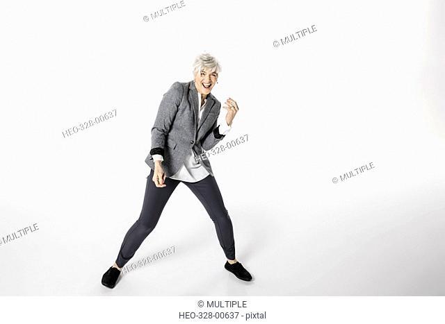 Portrait playful, energetic senior woman dancing against white background