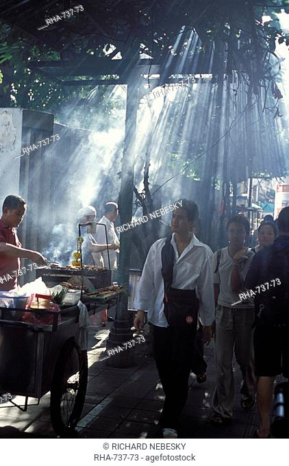 Street vendors selling grilled meat to passers-by on train platform, Bangkok, Southeast Asia, Thailand, Asia