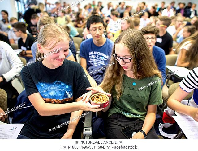14 August 2018, Germany, Braunschweig: Pupils Julia (L) and Friederike try canned lentils and spaetzle with sausage produced by the European Space Agency (ESA)...