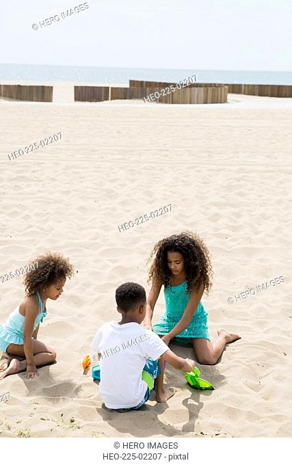 Brother and sisters making sandcastle at beach