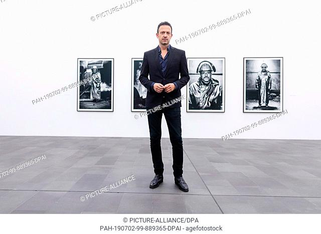 02 July 2019, North Rhine-Westphalia, Duisburg: Till Brönner, jazz musician and photographer, stands before his series with steel workers from Thyssenkrupp