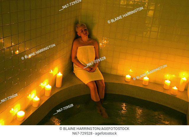 A woman relaxing in the whirlpool bath by candlelight, Temple Mountain Spa, Post Hotel & Spa, Lake Louise, Alberta, Canada