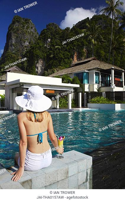 Woman relaxing by pool with drink in Bhu Nga Thani Resort and Spa, Railay, Krabi Province, Thailand MR