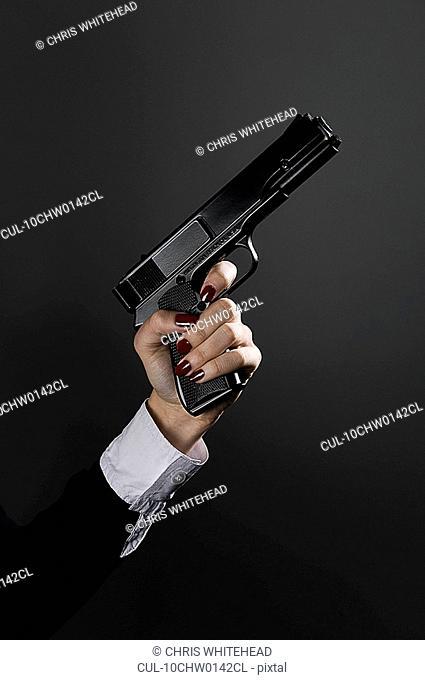 Female hand holding a gun