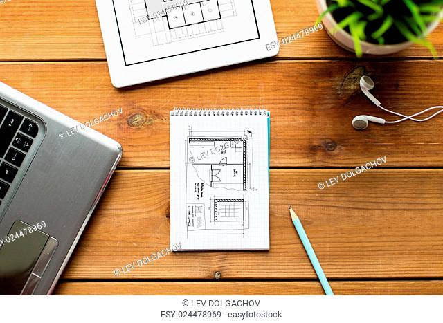 architecture, business, education and technology concept - close up of notebook, laptop and tablet pc computer with blueprint of room on wooden table