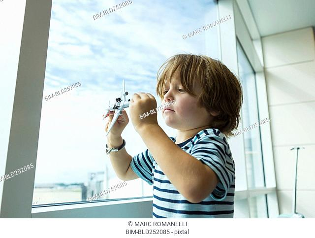 Caucasian boy playing with toy airplane near window