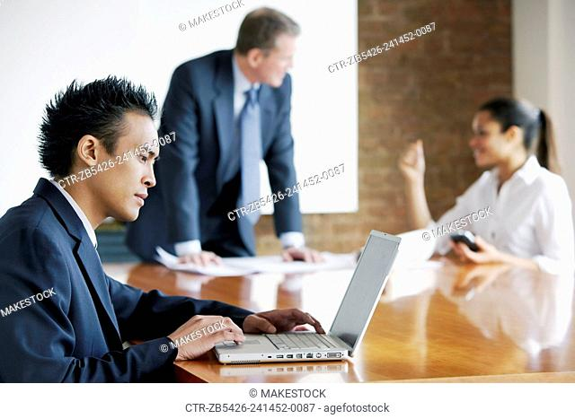 Businessman leaning on a boardroom table talking to woman executive. Young executive using laptop computer