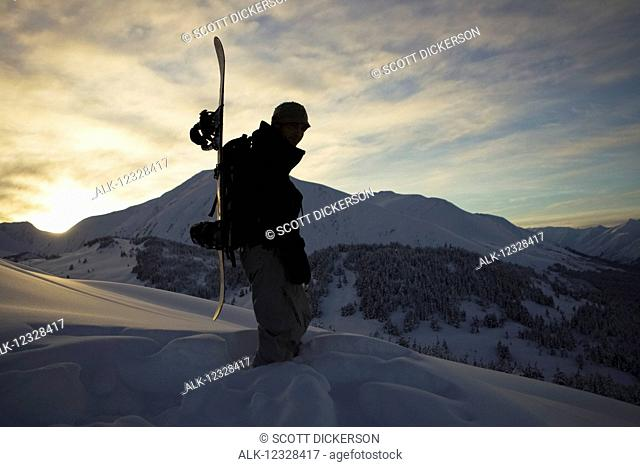 Snowboarder Silhouetted On A Mountaintop In Turnagain Pass, Southcentral Alaska, USA
