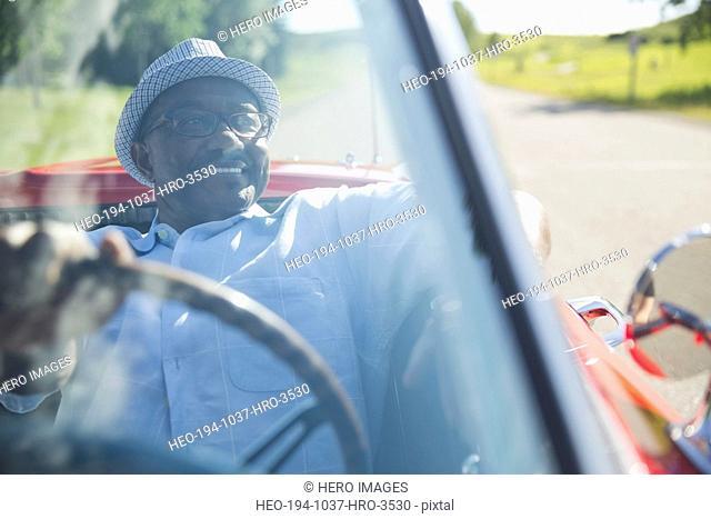 Smiling senior man driving red convertible